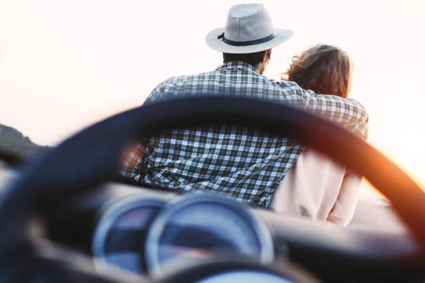 Trendige liebe paar Hipster auf Motorhaube Cabrio Autos sitzen und genießen Sie den Sonnenuntergang in Bergen – Foto