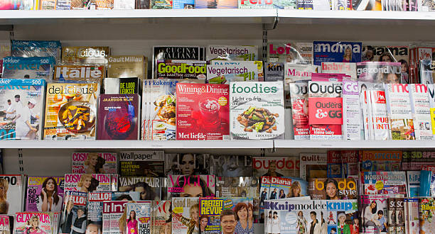 trendy magazines on shelf in bookstore Leiden The Netherlands-Januari 14, 2011: filled with Dutch fashion, food, hobby and trendy glossy magazines such as Cosmopolitan, Vogue, Wining and Dining, Vanity Fair, Glamour, Burda, Ouders, Mama.  magazine rack stock pictures, royalty-free photos & images
