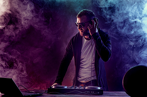 Young stylish man in glasses posing behind mixing console on colored smoke studio background.