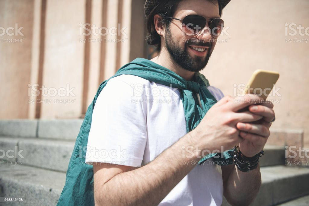 Trendy male person using cellphone outdoors - Royalty-free Adult Stock Photo