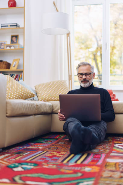 Trendy man relaxing on a carpet with a laptop stock photo