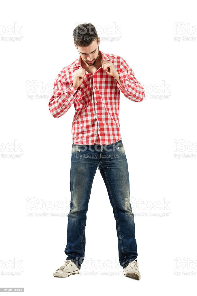 Trendy modern guy buttoning plaid shirt stock photo