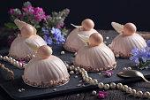 Trendy mousse cakes with pink mirror glaze. Dark background