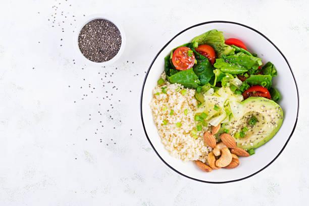Trendiger Salat. Vegane Buddhaschale mit Bulgur, Avocado, Gurke, Salat, Tomaten und Chiasamen. Internationaler Tag ohne Fleisch. Vegetarischer Salat. Ansicht von oben, über Kopf, flache Lage – Foto