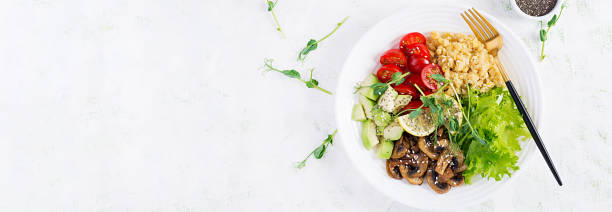 Trendy salad. Vegan Buddha bowl with lentil, avocado, mushrooms, lettuce, tomatoes and chia seeds. International Day Without Meat. Vegetarian salad. Top view, overhead, banner stock photo