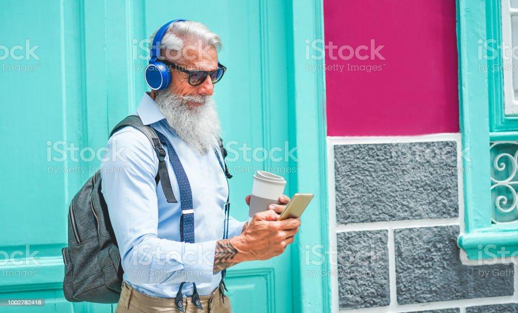 Homem sênior na moda usando música smartphone app e beber café no centro ao ar livre - macho de modo maduro se divertindo com a nova tecnologia tendências - Tech e o conceito de estilo de vida alegre e idosos - foto de acervo