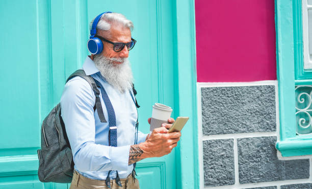Trendy senior man using music smartphone app and drinking coffee in downtown center outdoor - Mature fashion male having fun with new trends technology - Tech and joyful elderly lifestyle concept stock photo