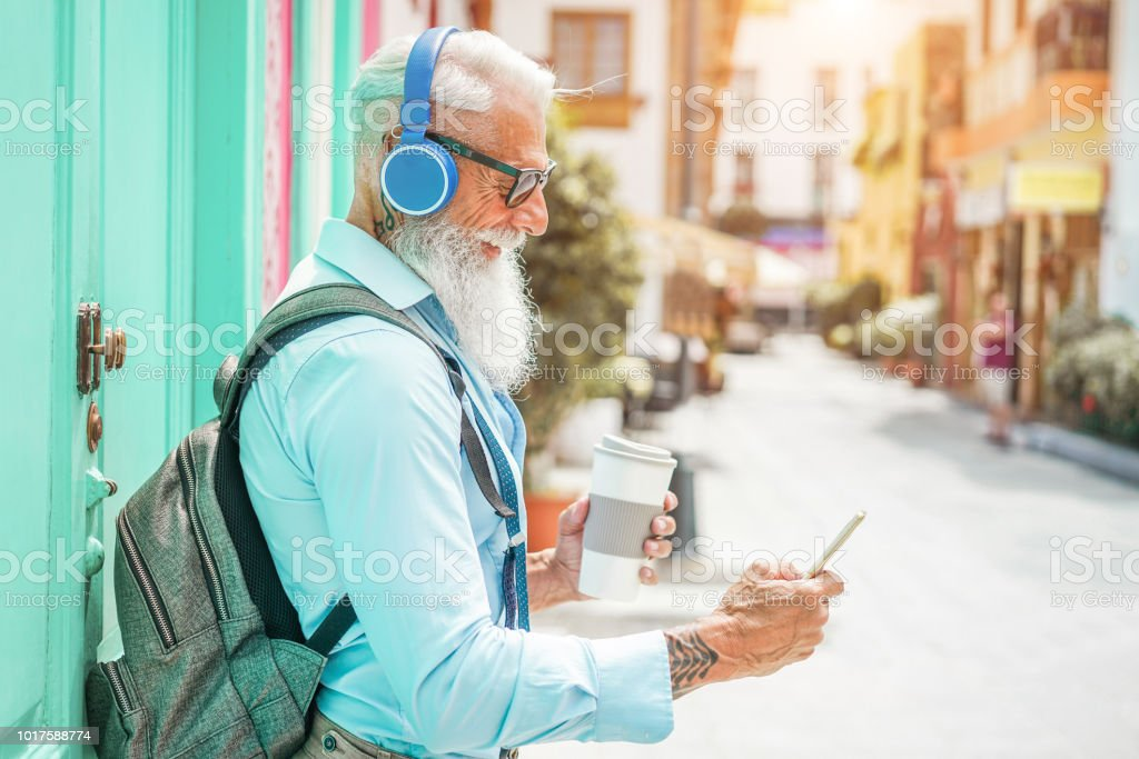 Trendy senior man using music smartphone app and drinking coffee in...