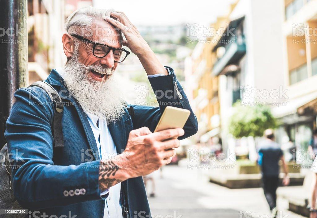 Na moda homem sênior usando smartphone app no centro ao ar livre - macho de modo maduro se divertindo com a nova tecnologia tendências - Tech e conceito de lifestyle idosos alegre - foco no rosto - foto de acervo