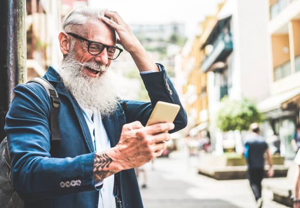 trendige senior woman mit smartphone-app in innenstadt outdoor - spaß mit neuen trends technologie reife mode-männlich - tech und freudige ältere lifestyle-konzept - konzentrieren sich auf seinem gesicht - alte tattoos stock-fotos und bilder