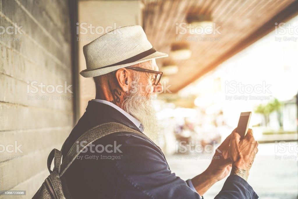 Na moda homem sênior usando smartphone app no centro ao ar livre - viajante de modo maduro se divertindo com a nova tecnologia tendências - Tech e conceito de lifestyle idosos alegre - foco na orelha - foto de acervo