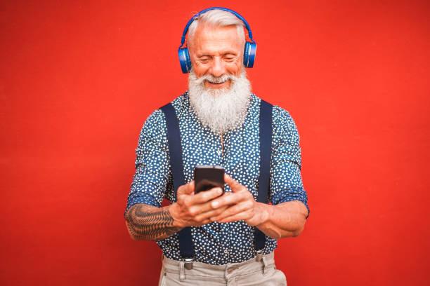trendiger senior-mann mit smartphone-app mit rotem backgorund-mature fashion rüde, die spaß an neuen trend-technologie haben-tech und fröhliches senioren-lifestyle-konzept-fokus auf seinem gesicht - alte tattoos stock-fotos und bilder