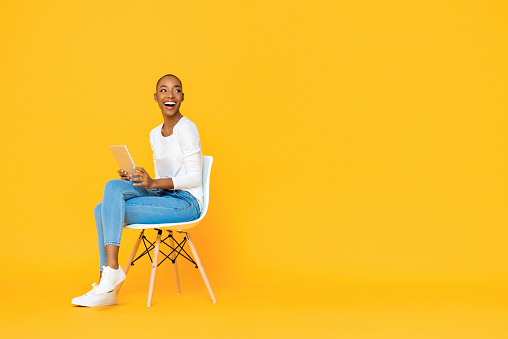 Trendy smiling African American woman sitting on a chair using tablet computer thinking and looking at empty space aside isolated yellow background