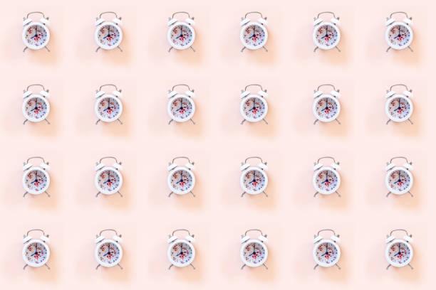 Padrão de primavera e verão da moda feito com relógio feliz em fundo pastel rosa - foto de acervo