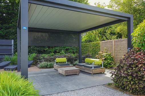 Trendy sunloungers and overhang with trendy garden furniture.