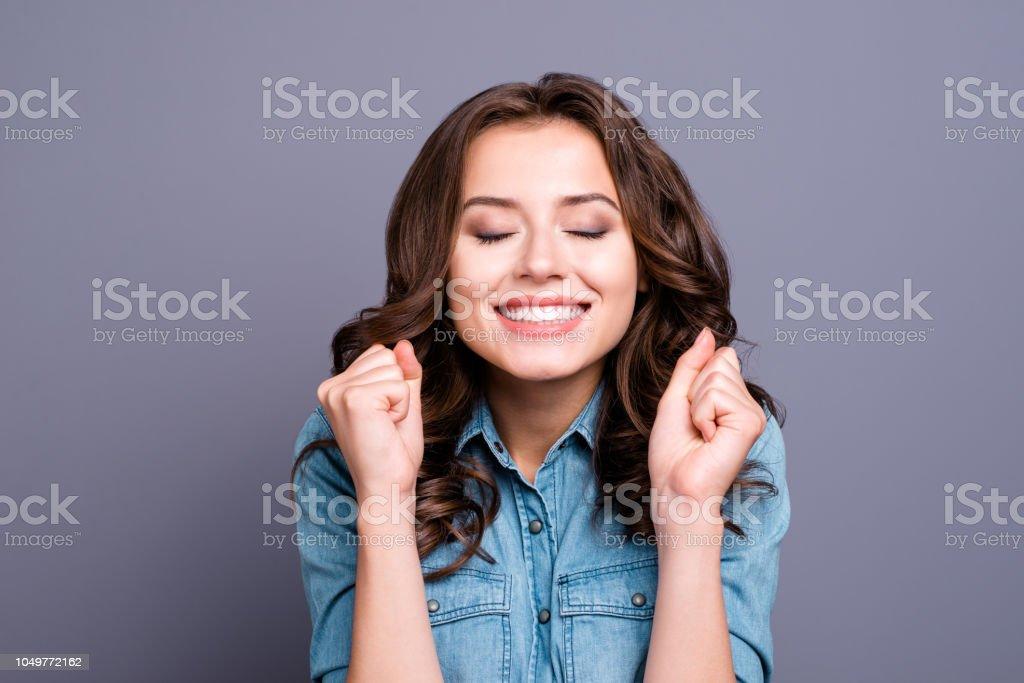 Trendiges süße zarte herrliche schönes fröhliches liebenswert schöne attraktive stilvolle Brünette Mädchen mit lockigem Haar im lässigen Denim-Bluse, zeigt Glück Geste, schloss die Augen, auf grauem Hintergrund isoliert – Foto