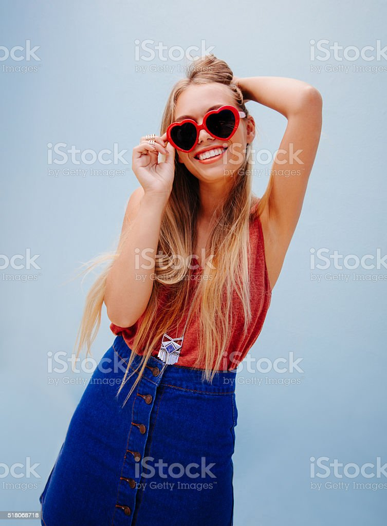 Trendy teenage blond model with heart shape sunglasses stock photo