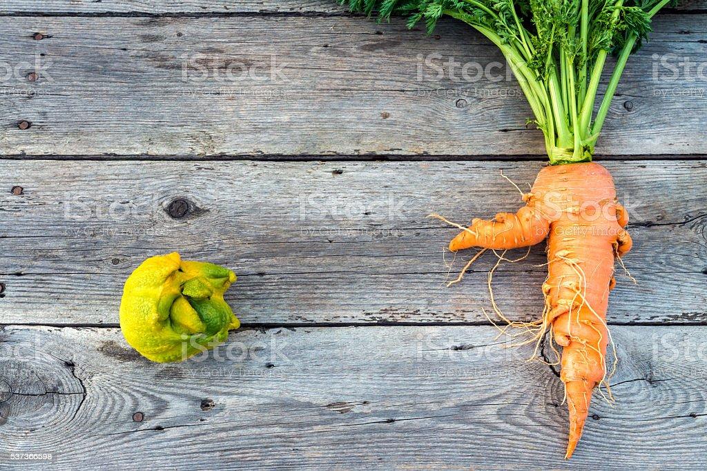 Trendy ugly carrot and lemon on barn wood stock photo