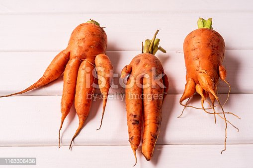 Flat lay Some ugly curved carrots on white wooden background.