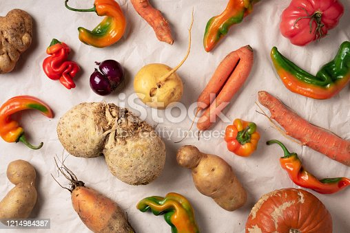 Trendy ugly organic vegetables. Assortment of fresh eggplant, onion, carrot, zucchini on green background. Top view. Cooking ugly food concept. Non gmo vegetables.