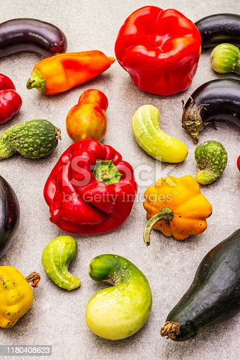 Trendy ugly organic vegetables. Assortment of fresh pepper, eggplant, cucumber, tomato, pumpkin. Cooking ugly food concept. Stone concrete background