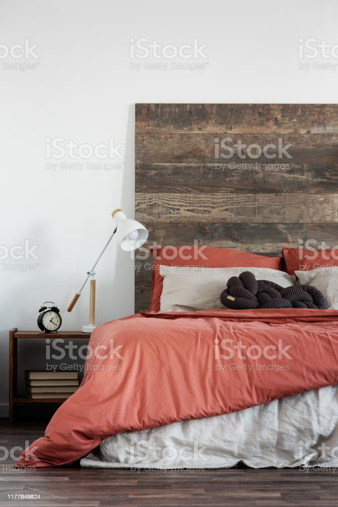 Trendy White Lamp Next To Black Clock On Wooden Nightstand Next To King Size Bed With Wooden Headboard Stock Photo Download Image Now Istock