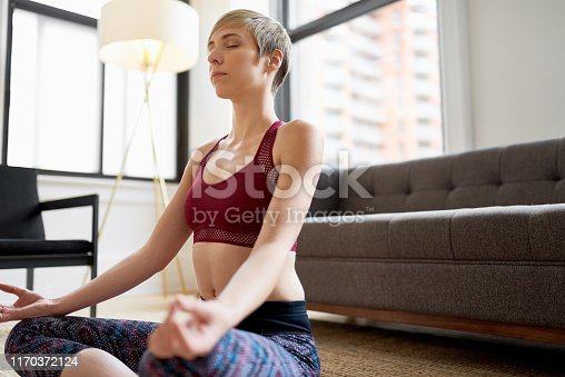 916126594istockphoto Trendy woman doing yoga as part of her mindfulness morning routine 1170372124