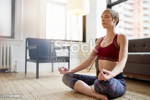 916126594istockphoto Trendy woman doing yoga as part of her mindfulness morning routine 1171010083