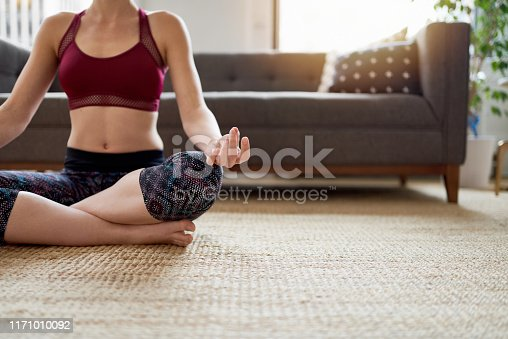 916126594istockphoto Trendy woman doing yoga as part of her mindfulness morning routine 1171010092