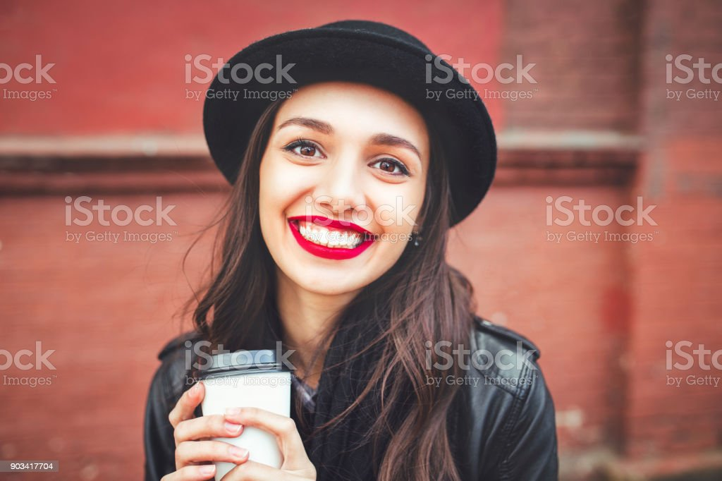 Trendy woman in hat with drink outdoor. Young woman with red lips in black hat stock photo