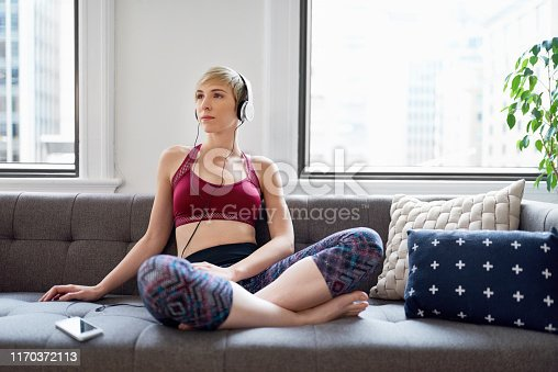 916126594 istock photo Trendy woman listening to a meditaion app as part of her mindfulness morning routine 1170372113