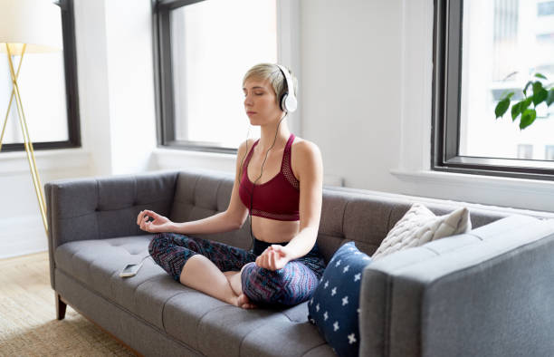 Trendy woman listening to a meditaion app as part of her mindfulness morning routine stock photo