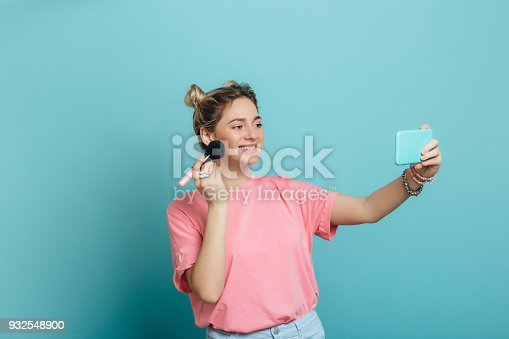 istock trendy woman - making make-up and selfie at blue background 932548900