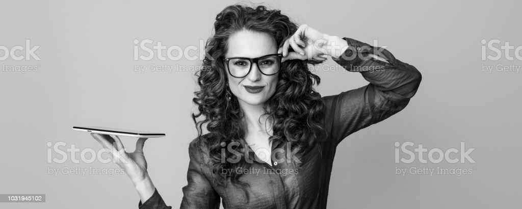 trendy woman with long wavy brunette hair with tablet PC on background
