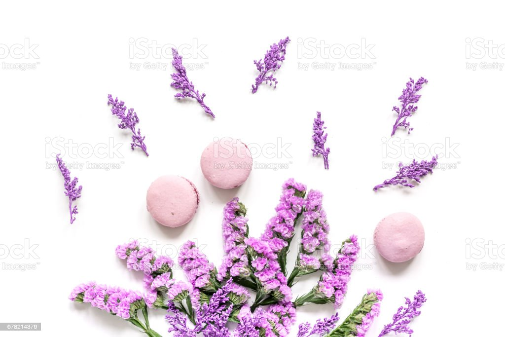 Trendy woman pattern with flowers and macaroons on plate top view stock photo