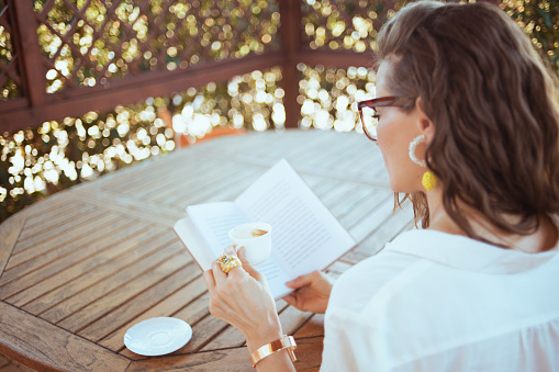 trendy woman sitting at table drinking coffee and reading book