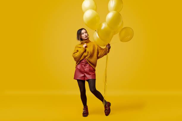 femme à la mode avec des ballons jaunes - fond couleur uni photos et images de collection