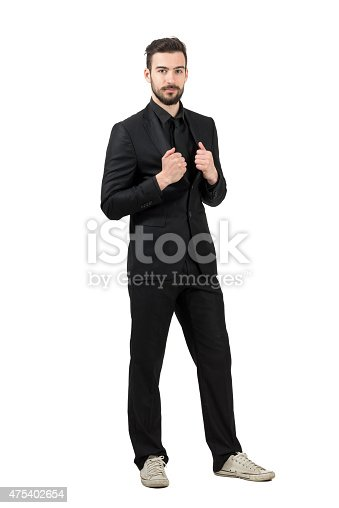 498403166 istock photo Trendy young bearded businessman wearing white sneakers and black suit 475402654