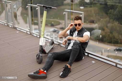 Trendy young hipster man in stylish summer gray  jeans clothes in sunglasses with a modern electric scooter sits on a wooden floor near a glass wall outdoors. Handsome american guy model is resting.