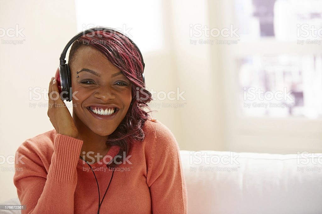 Trendy young lady listening to music on headphones royalty-free stock photo