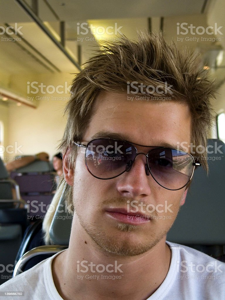 Trendy young man sitting in plane royalty-free stock photo