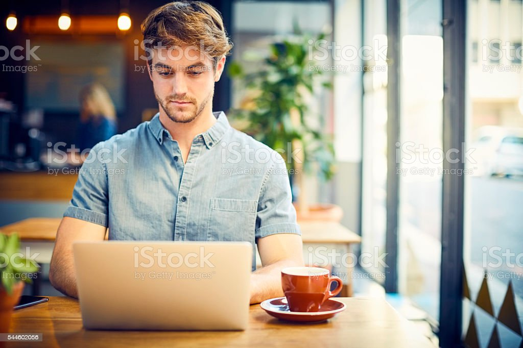 Trendy young man using laptop in cafe stock photo