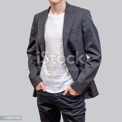 Trendy young man wearing grey blazer and dark jeans, standing against a grey background. design and people concept