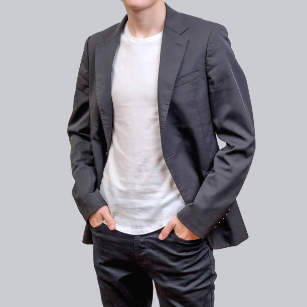 Trendy young man wearing grey blazer and dark jeans, standing against a grey background. Trendy young man wearing grey blazer and dark jeans, standing against a grey background. design and people concept blazer jacket stock pictures, royalty-free photos & images