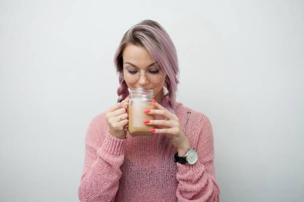 Mujer joven de moda bebiendo café batido. Chica con jarra-taza en - foto de stock
