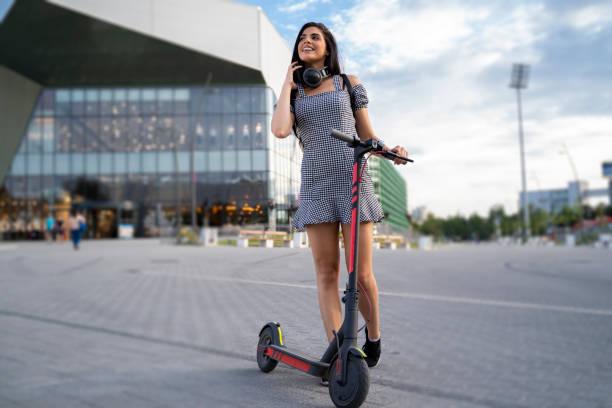 trendy young woman in the city with her e scooter - monopattino elettrico foto e immagini stock