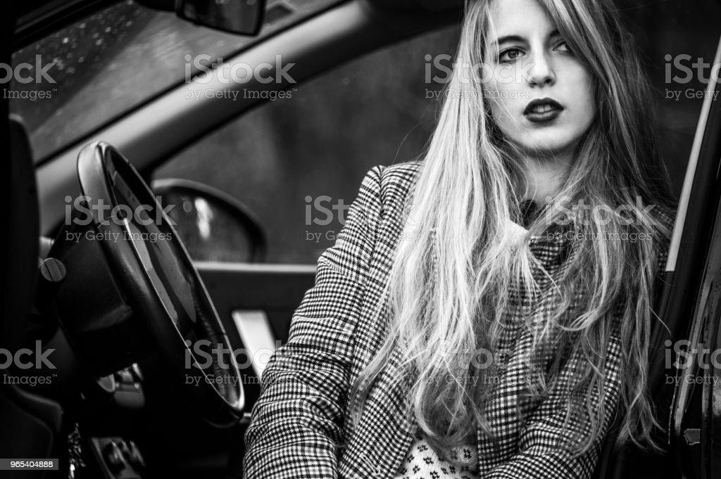 유행 젊은 여자는 밖으로 다리 열린 문, 차에 앉아. - 로열티 프리 가리기 스톡 사진