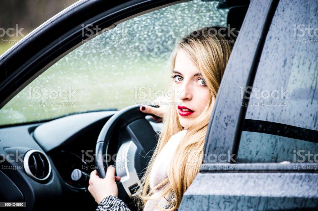 Mode jeune femme est assise dans une voiture avec porte ouverte, jambes dehors. - Photo de A la mode libre de droits