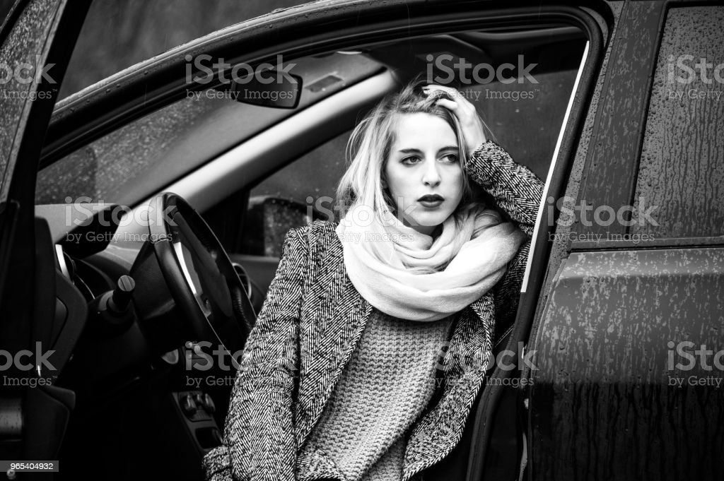 Trendy young woman is sitting in a car with opened door, legs out. royalty-free stock photo