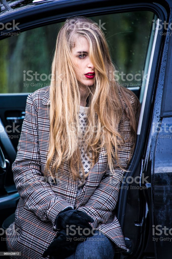 Trendy young woman is sitting in a car with opened door, legs out. zbiór zdjęć royalty-free